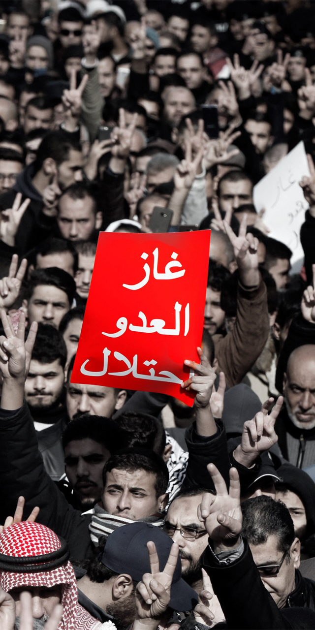 """Jordanian demonstrators chant slogans during a protest against a government agreement to import natural gas from Israel, in Amman, Jordan, January 3, 2020. The red placard reads: """"The enemy's gas is occupation"""". REUTERS/Muhammad Hamed"""